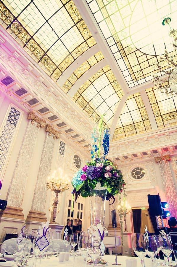 Tabelle mit Blumen in der Banketthalle stockfotos