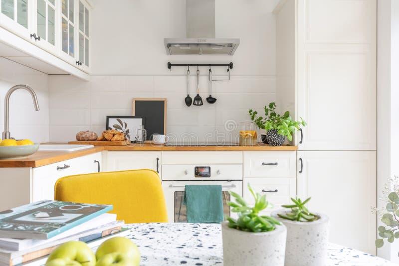 Tabelle mit Frucht, Anlagen und Zeitschriften in einem hellen Kücheninnenraum Schränke im Hintergrund Reales Foto stockbilder