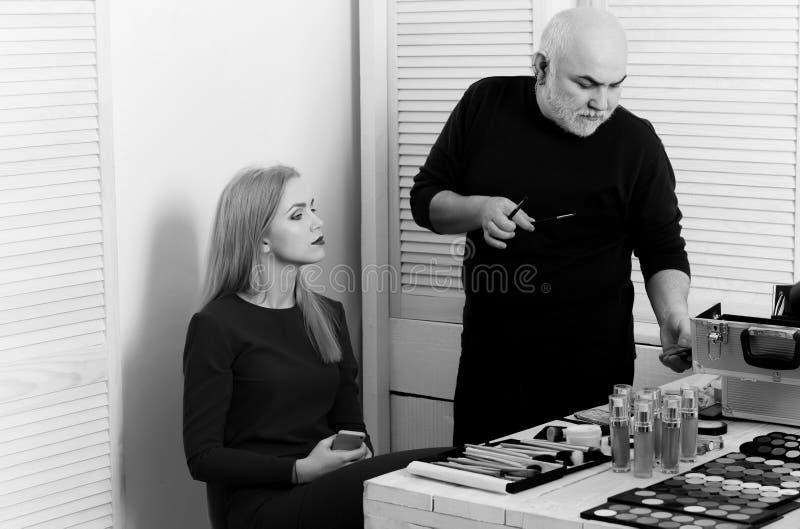 Tabelle mit kosmetischer Ausrüstung visage Mann, der Handy mit Make-upbürsten überprüft stockbild