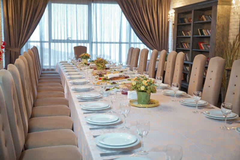 Tabelle mit leeren Platten und Gläsern im Restaurant Kristallweingläser auf einem gedienten Bankettisch mit Salaten und stockbild