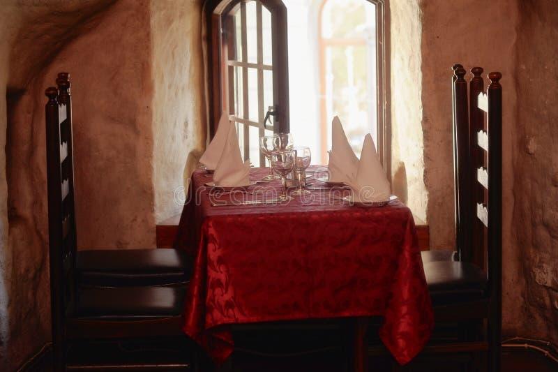 Tabelle mit roter Tischdecke und Holzstühlen stockfoto
