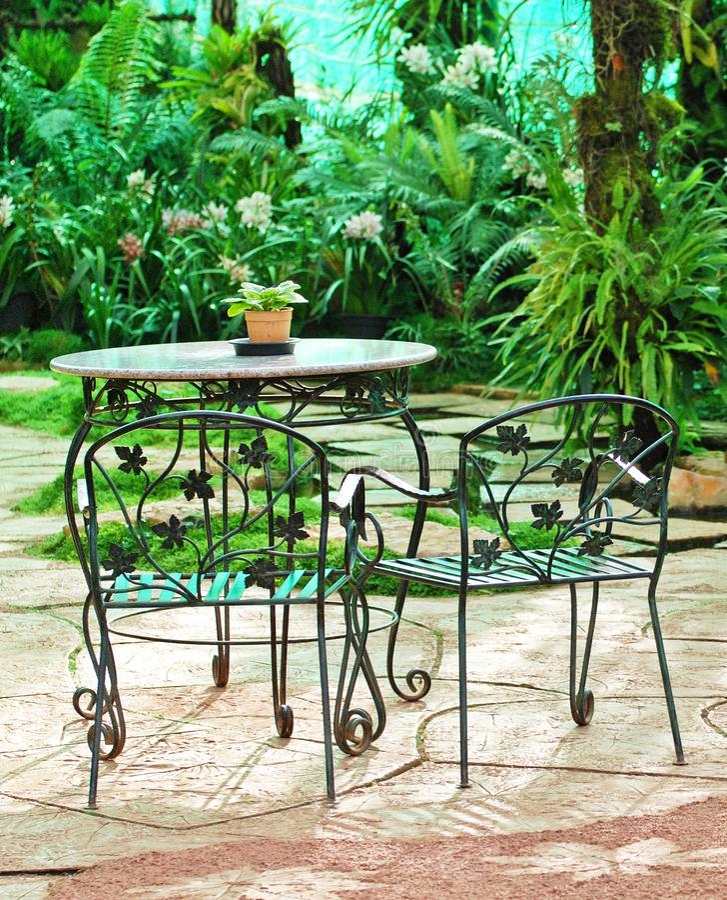 Tabelle mit Stühlen im Garten lizenzfreie stockbilder