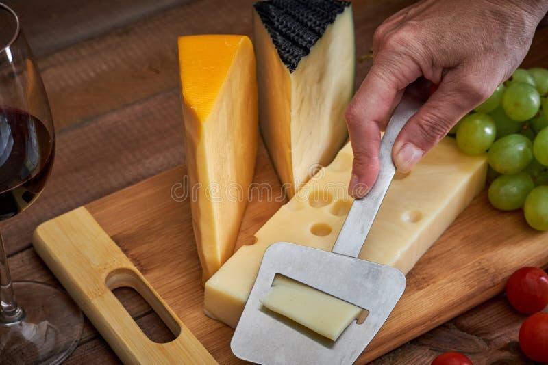 Tabelle mit unterschiedlichen Käsen und Weinglas auf dunklem Hintergrund lizenzfreie stockfotos