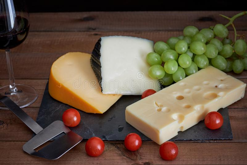 Tabelle mit unterschiedlichen Käsen und Weinglas auf dunklem Hintergrund stockbild