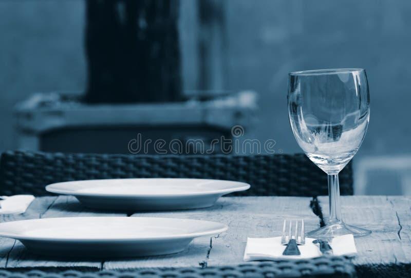 Tabelle mit Weinglas und großen Tellern in einem Garten lizenzfreie stockbilder