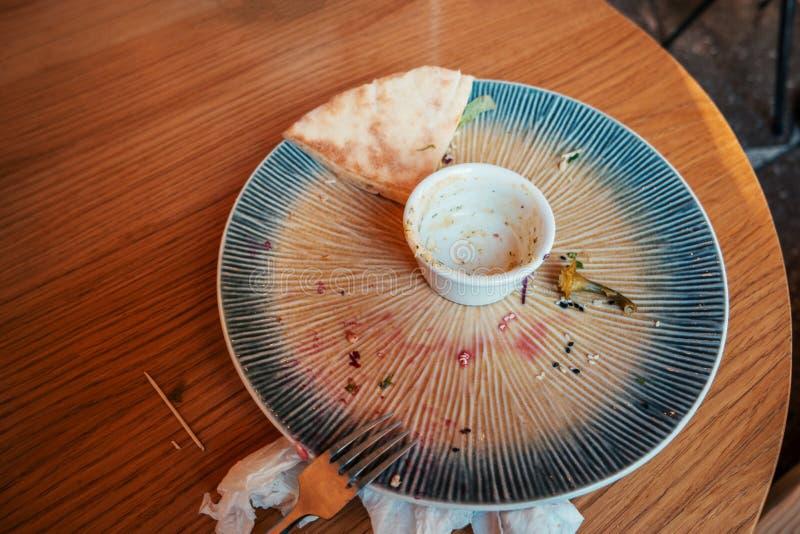 Tabelle nachdem dem Essen mit leerer Platte und Überresten auf ihr stockfoto