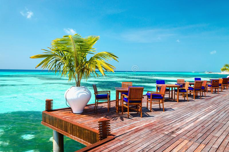 Tabelle und Stühle am Wasserrestaurant am Hintergrund des blauen Himmels, Malediven-Insel stockbild