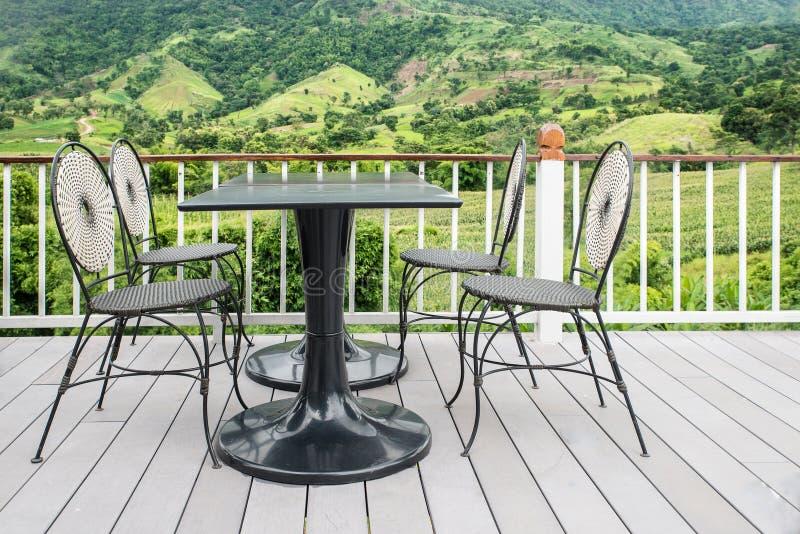 Tabelle und Stuhl auf Terrasse mit Natur im Hintergrund lizenzfreie stockfotos