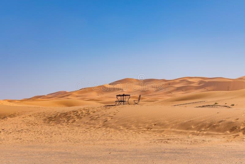 Tabelle und Stuhl im Abstand auf einer Sanddüne in Sahara Desert lizenzfreie stockbilder