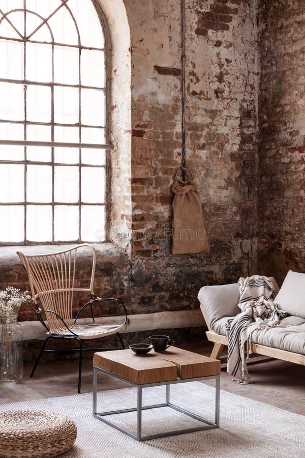 Tabelle zwischen Puff und Couch im Wohnzimmerinnenraum mit Fenster über Lehnsessel lizenzfreies stockfoto