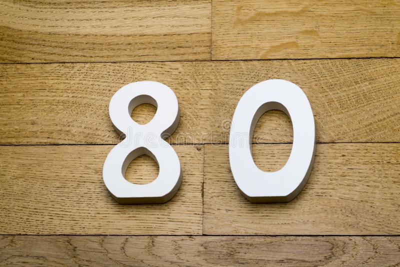 Tabellen achtzig auf dem hölzernen, Parkettboden lizenzfreie stockfotos