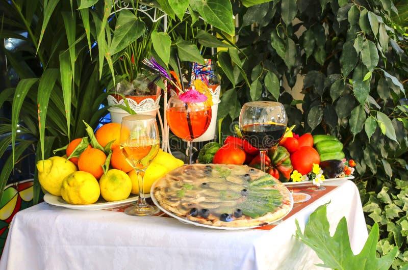 Tabellen dekorerade med traditionell italienare för pizza, för frukt och för vin royaltyfri bild