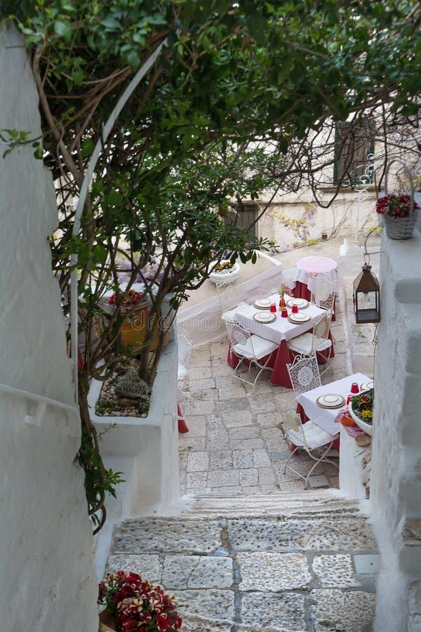 Tabellen eines Restaurants in einem Durchgang in Ostuni Italien lizenzfreie stockfotos