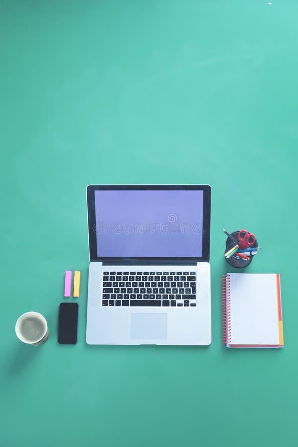 Tabellen för kontorsskrivbordet med bärbara datorn, den smarta telefonen, koppen kaffe och tillförsel som isoleras på grön bakgru royaltyfria foton