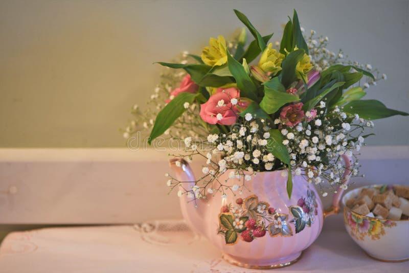 Tabellen med den gammalmodiga tekanna- och sockerbunken fyllde med nya blommor arkivbild