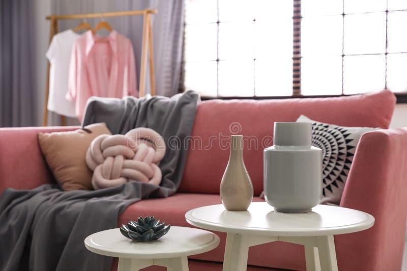 Tabellen mit stilvollen Vasen und Zierpflanze im Wohnzimmerinnenraum stockbilder