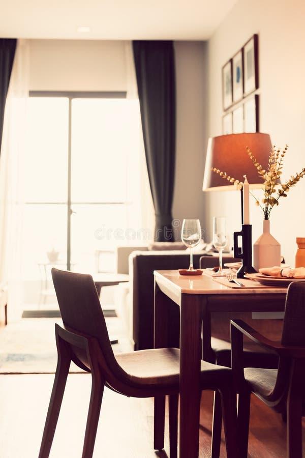 Tabellen och det maträtt-, lamp- och vinexponeringsglaset är i hotellrummet Fönster för naturligt ljus utifrån royaltyfria bilder