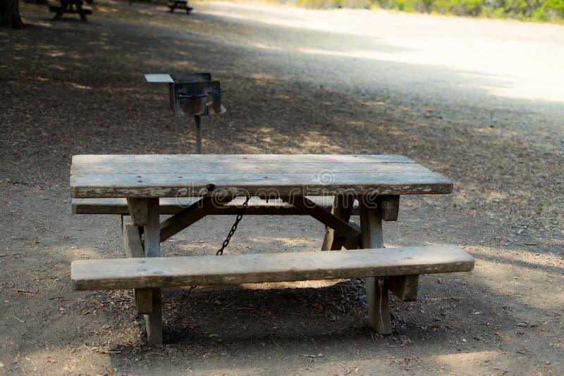 Tabellen och stol med kolgallret i parkerar royaltyfria bilder