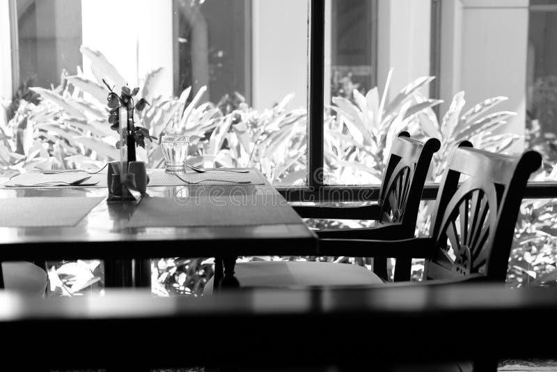 Tabellen- u. Stuhlcafékaffeestuberestaurantinnenraum nahe Garten stockfoto