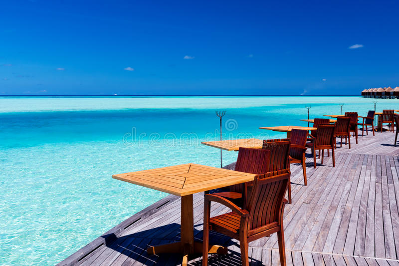 Tabellen und Stühle an der tropischen Strandgaststätte stockfotos