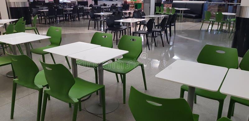 Tabellen und Stühle in einer Gastronomiebereichcafeteria stockfoto