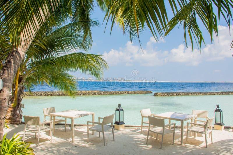 Tabeller och stolar i den lyxiga utomhus- restaurangen på den tropiska ön royaltyfri bild
