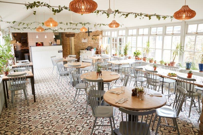 Tabeller och stolar i en tom restaurang i ljust dagsljus royaltyfri fotografi