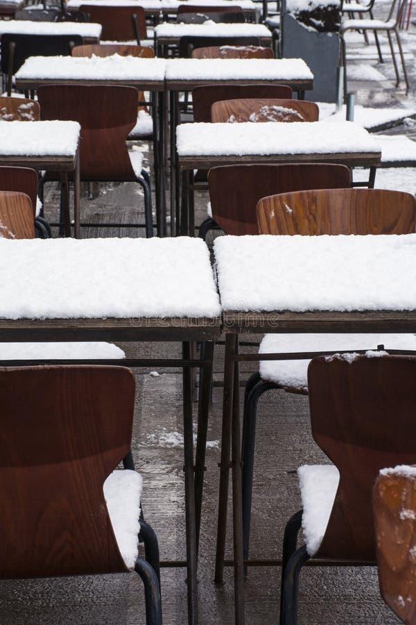 Tabeller och stolar på gatan i snö royaltyfri bild