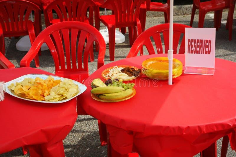 Tabeller under en röd bordduk med disk av chips, frukt och ett reserverat tecken royaltyfri foto