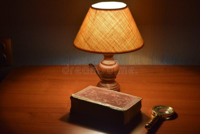 Tabelllampa, gammal bok och förstoringsapparat på skrivbordet fotografering för bildbyråer