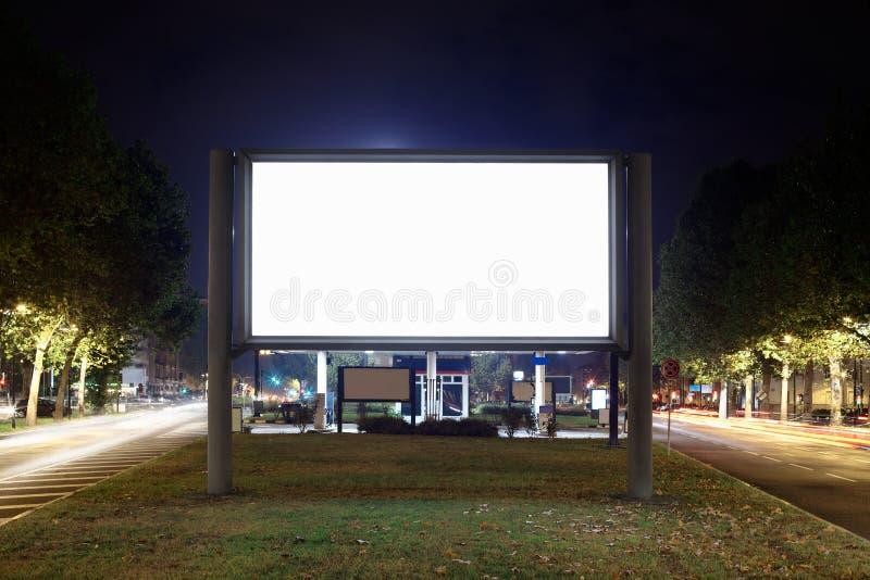Tabellone per le affissioni in bianco alla notte fotografia stock