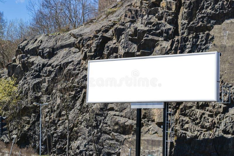 Tabellone per le affissioni bianco in bianco sulla via della città Nella via e nelle rocce del fondo Derisione su Manifesto sulla fotografia stock