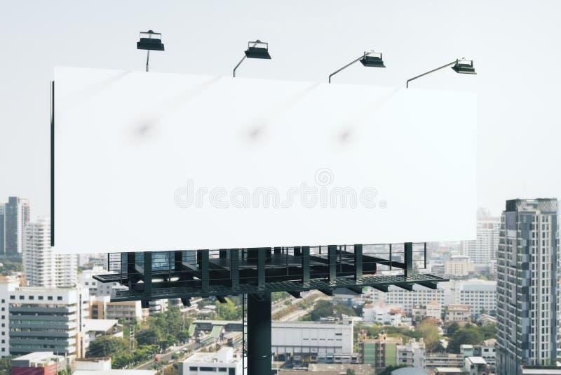 Tabellone per le affissioni bianco vuoto in città fotografia stock libera da diritti