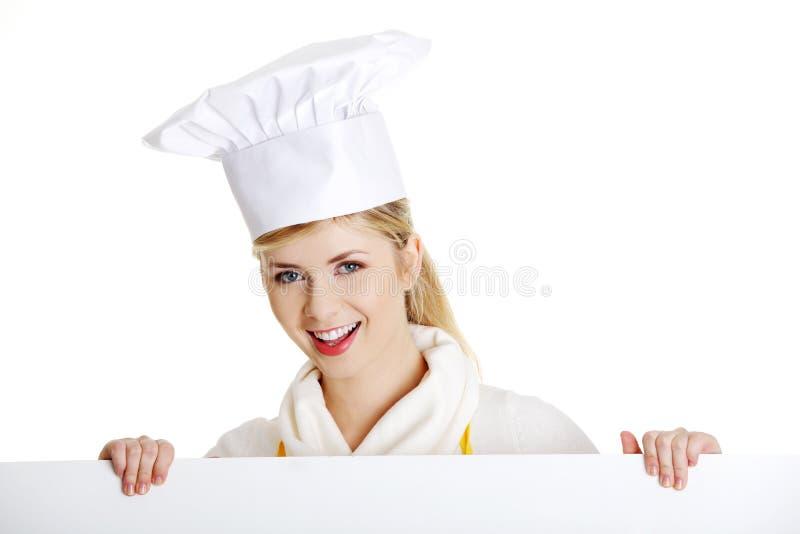 Tabellone per le affissioni felice del segno della holding del cuoco o del panettiere della donna. fotografia stock