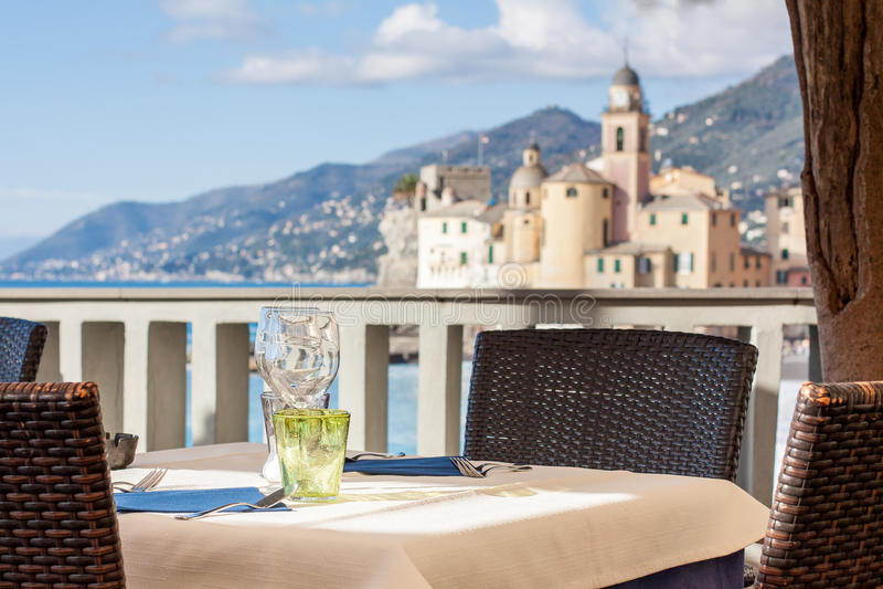 Tabelluppsättning i italiensk restaurang framme av den Camogli fjärden, near Ge royaltyfria bilder