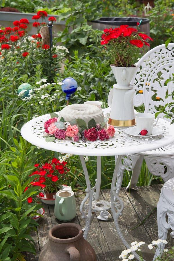 Tabelluppsättning i trädgård med blommor lite varstans arkivbild