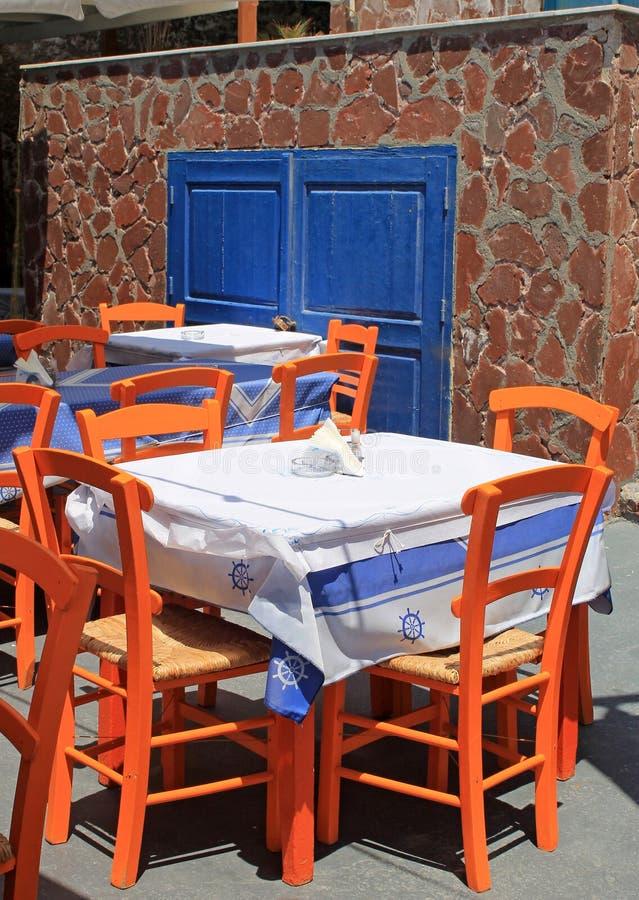 Taberna grega com as cadeiras de madeira alaranjadas pela costa de mar, Grécia, imagem de stock