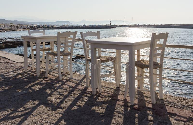 Taberna grega com as cadeiras de madeira alaranjadas pela costa de mar, Grécia, ilha de Santorini em Cyclades Foco seletivo imagem de stock