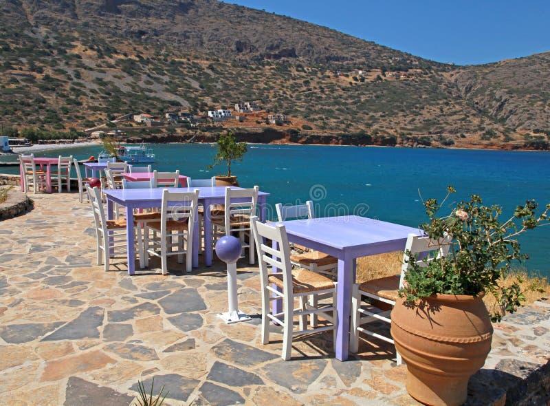 A taberna grega com as tabelas cor-de-rosa e lilás e o branco preside o overloo foto de stock