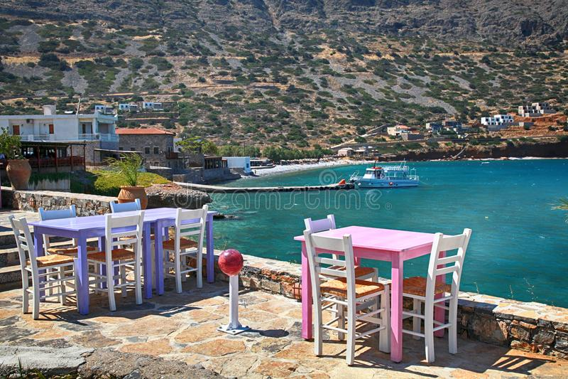 A taberna grega com as tabelas cor-de-rosa e lilás e o branco preside o overloo foto de stock royalty free