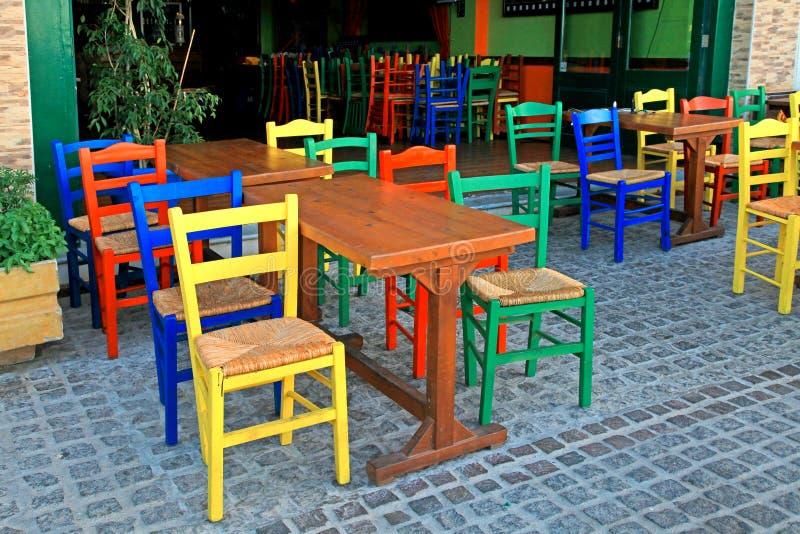 Taberna grega com tabela de madeira e as cadeiras coloridos, Creta, Gree imagem de stock royalty free