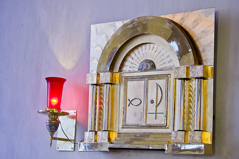 Catholic tabernacle with ligth representin presence of God. Tabernacle with lit candle representing the presence of God royalty free stock images