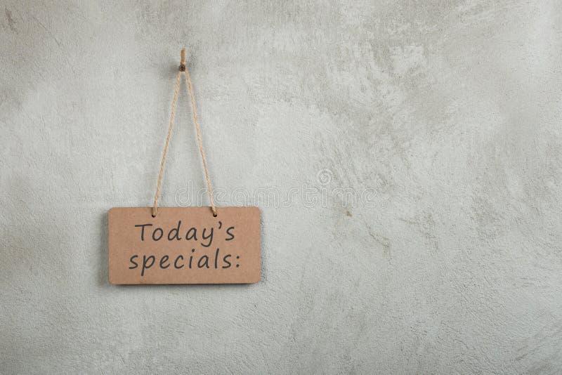 tablón de anuncios, pizarra, pizarra con el texto Today' specials de s en la pared gris del cemento del espacio de la copia imágenes de archivo libres de regalías