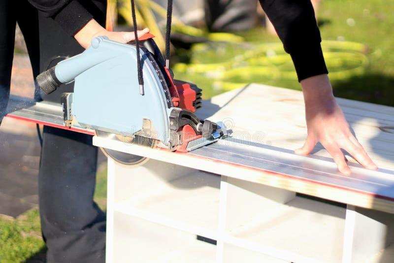 Tablón de madera que asierra de la mujer imagen de archivo