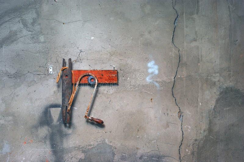 Tablón de madera rojo con Rusty Manual Jigsaw, una junta de goma, la manguera plástica torcida y una ejecución de la pieza del hi fotos de archivo