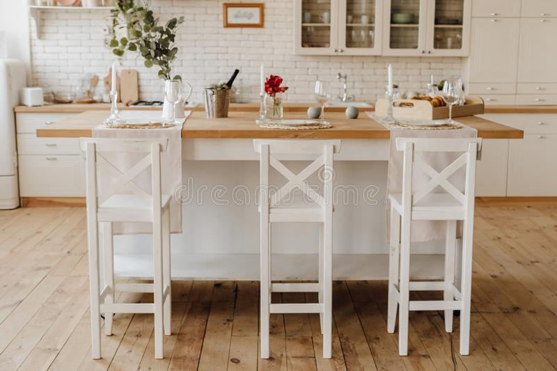 Tabla acogedora blanca de la isla de cocina en casa interior fotos de archivo libres de regalías