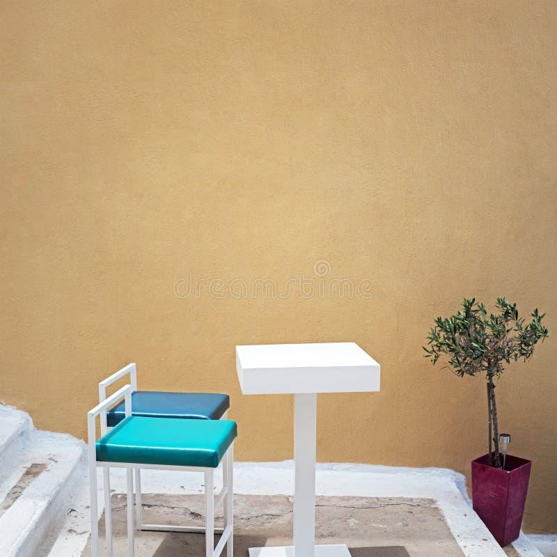 Tabla al aire libre y dos sillas cerca de la pared del grunge fotos de archivo