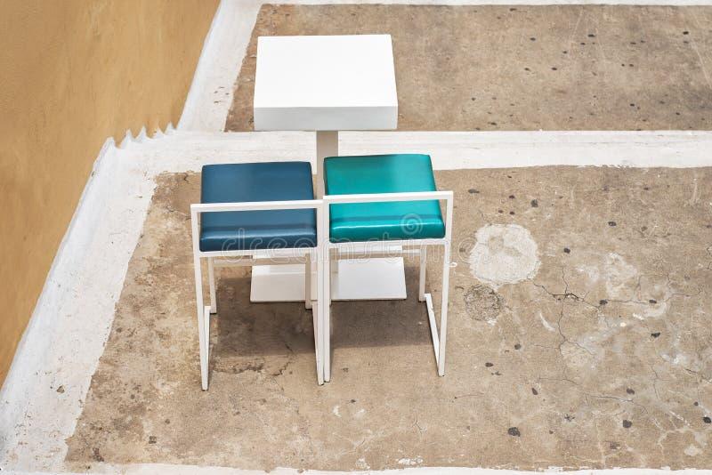 Tabla al aire libre y dos sillas cerca de la pared del grunge imagenes de archivo