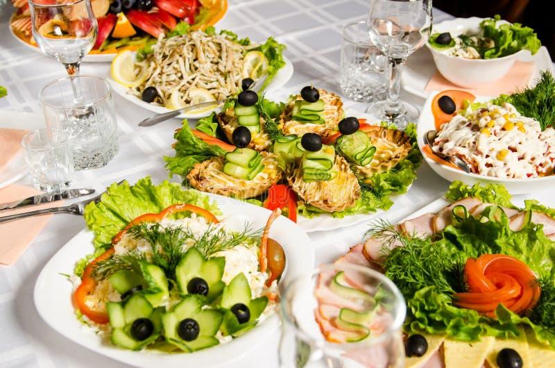 Tabla alineada con la variedad de platos de los cuales la pieza central es plato con varios tartlets con el pollo, jamón, pepinos fotografía de archivo libre de regalías