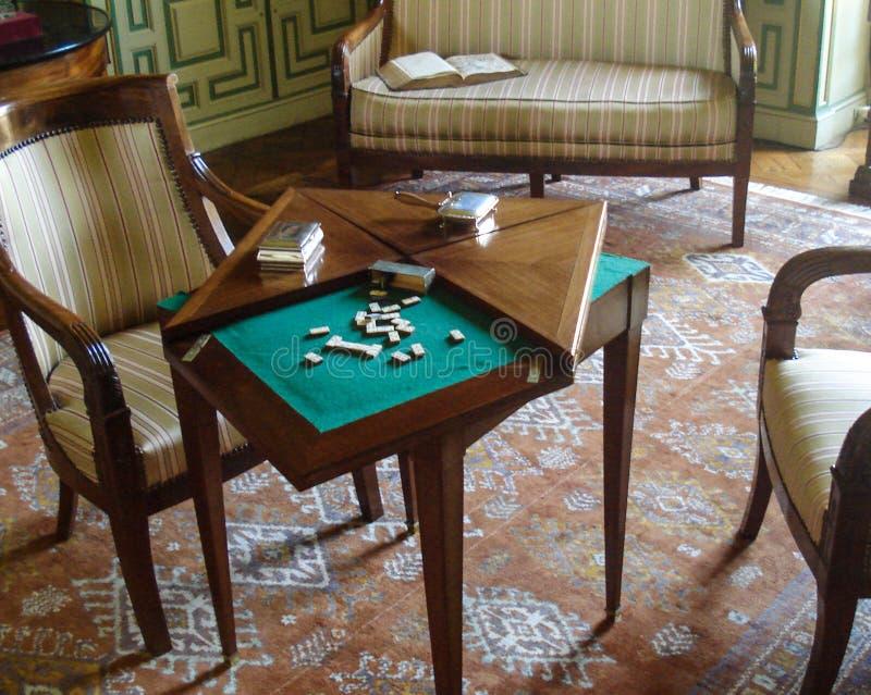 Tabla antigua con el juego incorporado del dominó Situado en un cuarto clásico adornado foto de archivo libre de regalías
